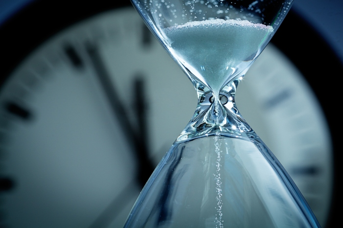 A hourglass with falling sand in front of a clock reaching midnight. Concept photo urgency, and time is running out and deadline is approaching. Close-up of hour glass is photographed in horizontal format with copy space, against a soft-focus clock face in the background.