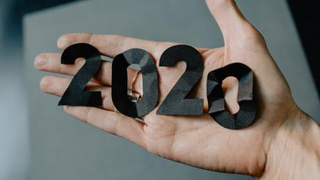 crumpled cutout numbers 2020 showing on person's open palm